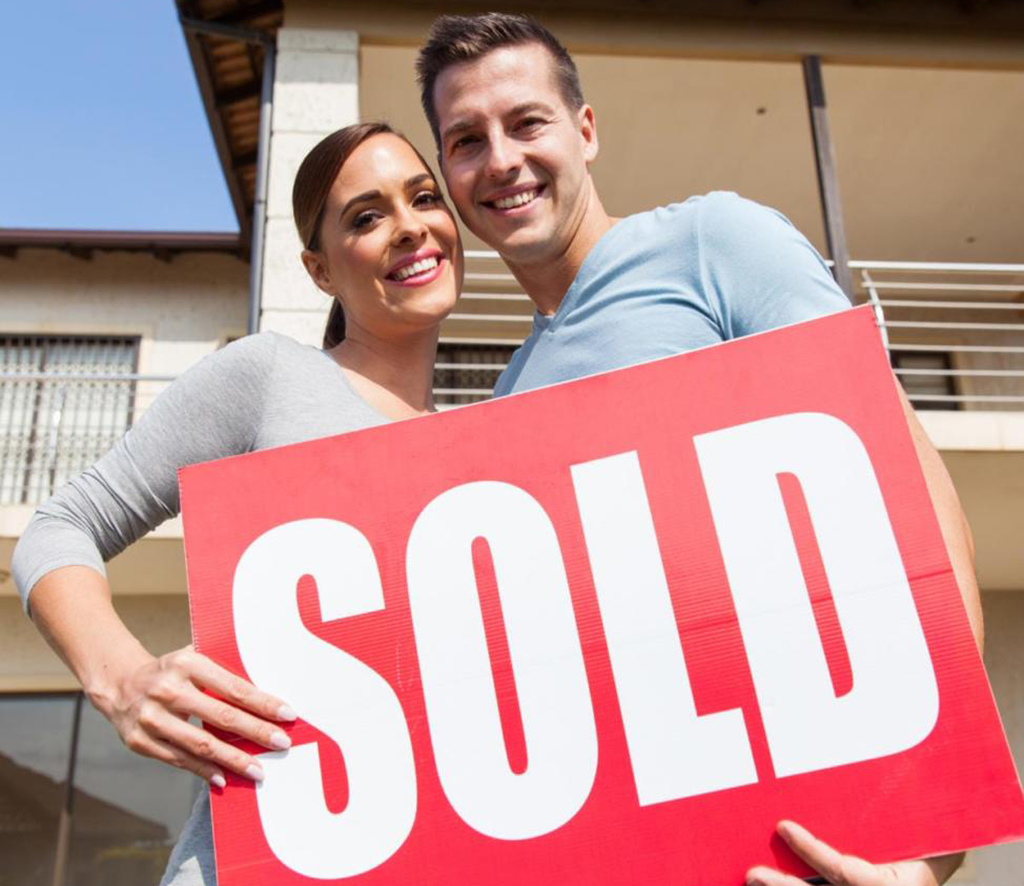 Happy couple holding real estate sold sign